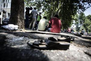 Alcuni migranti accampati vicino alla stazione Tiburtina (foto ANSA/ANGELO CARCONI)